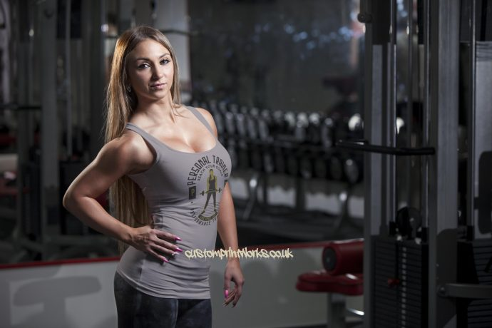 grey personal trainer vest with woman holding a barbell