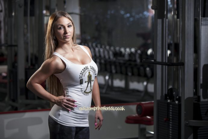 white personal trainer vest with woman holding a barbell